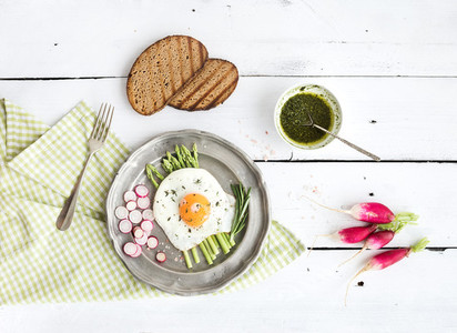 Healthy breakfast set  Fried egg with asparagus  radishes  green sauce and bread on vintage metal plate over white wooden backdrop