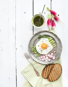 Healthy breakfast set  Fried egg with asparagus  radishes  green sauce and bread on vintage metal plate over white wooden backdrop  top view