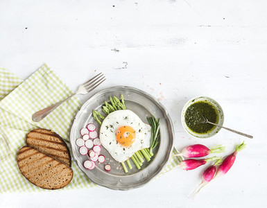 Healthy breakfast set  Fried egg with asparagus  radishes  green sauce and bread