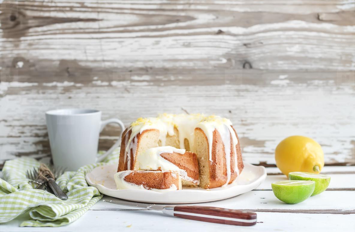 Moist lime and lemon bundt yoghurt cake  white rustic wooden  background