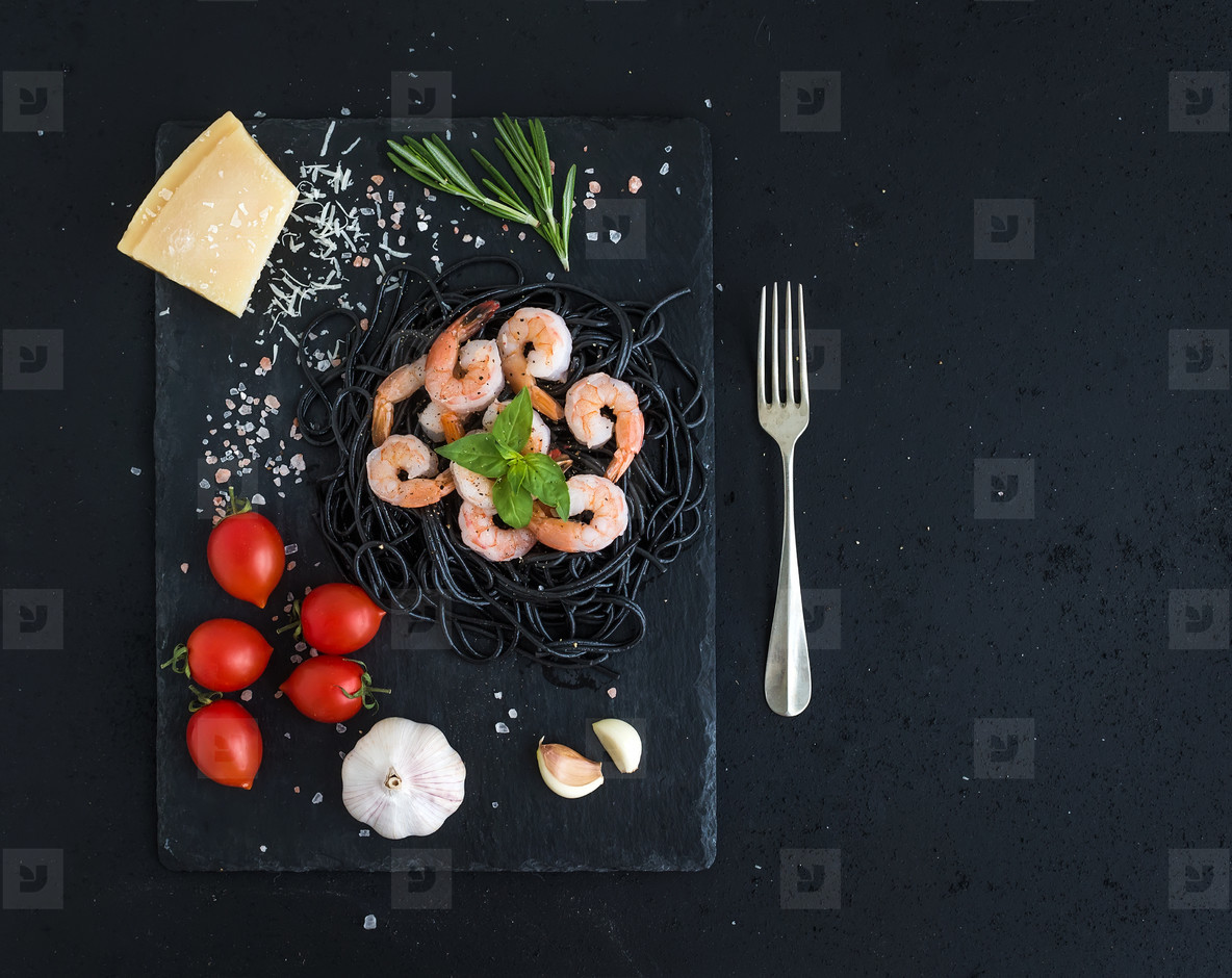 Black pasta spaghetti with shrimps  basil  pesto sauce  garlic  parmesan cheese and cherry tomatoes on a slate tray over black grunge backdrop  top view