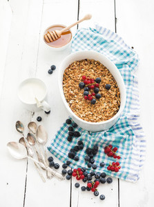 Healthy breakfast  Oat granola berry crumble with fresh blueberries  yogurt and honey in ceramic baking dish over white rustic backdrop