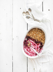 Healthy breakfast Oat granola berry crumble with  in ceramic baking dish over white rustic backdrop half eaten