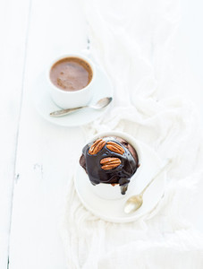 Tasty homemade brown muffin with chocolate ganache icing  pecan nuts and coffee in separate bakind cup