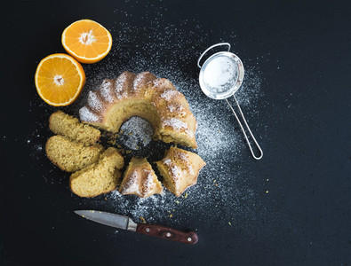 Moist orange bundt yoghurt cake with sugar powder on top  dark grunge background