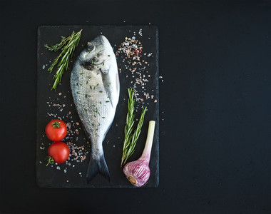 Fresh uncooked dorado or sea bream fish with vegetables  herbs and spices on black slate tray over dark grunge backdrop  top view
