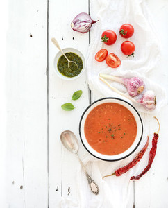 Gazpacho soup in rustic metal bowl with fresh tomatoes green sauce chili garlic and basil over white wooden backdrop Top view
