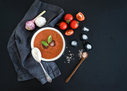 Gazpacho soup in rustic metal bowl with fresh tomatoes  ice cubes  garlic and basil over dark grunge backdrop