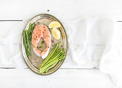 Raw salmon steak with asparagus lemon spices and rosemary on vintage silver tray over white wooden backdrop top view