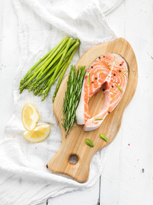 Raw salmon steak with asparagus  lemon  spices and rosemary on rustic wooden chopping board over white backdrop  Top view