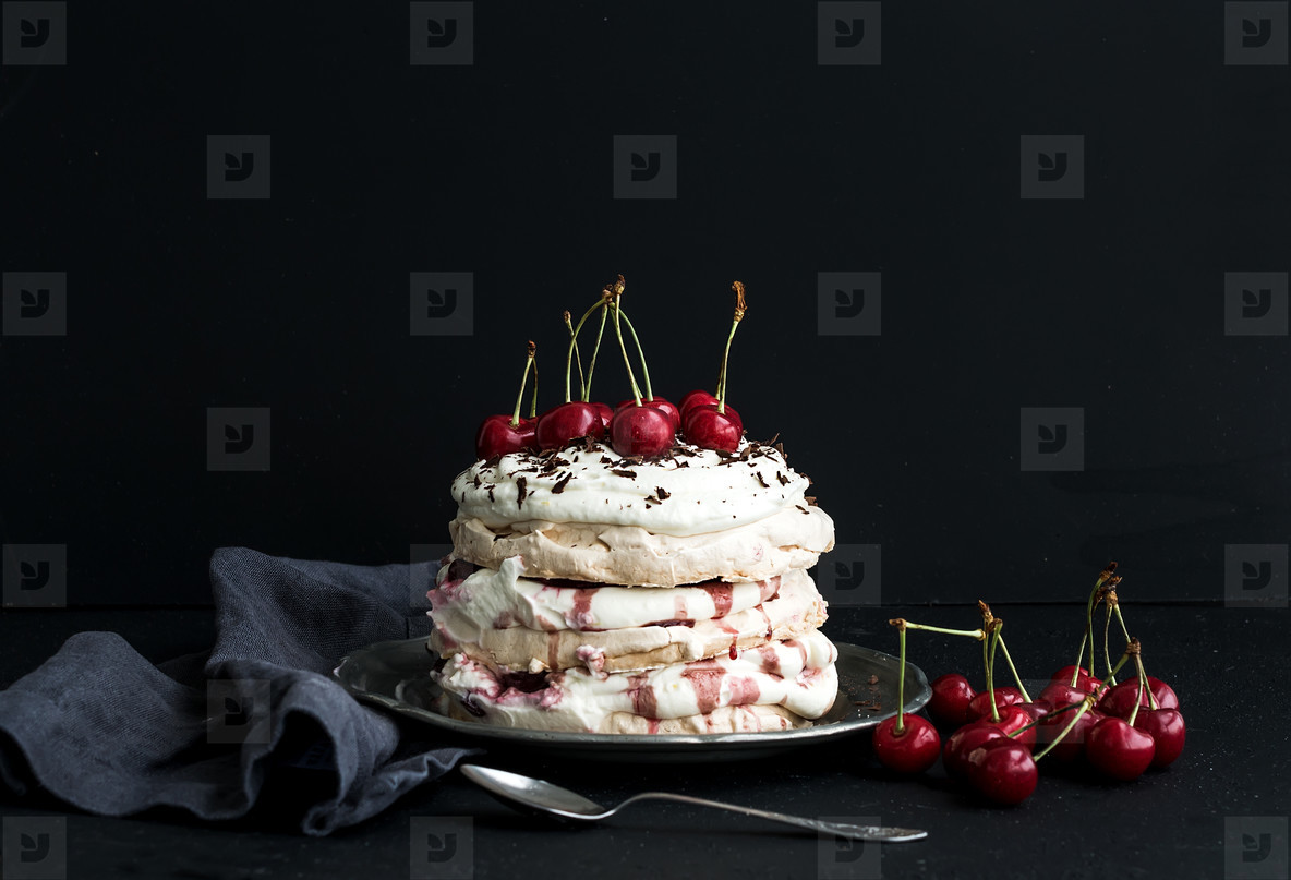 Pavlova cake with fresh cherry  cheese cream and chocolate chips in vintage silver plate over dark grunge background