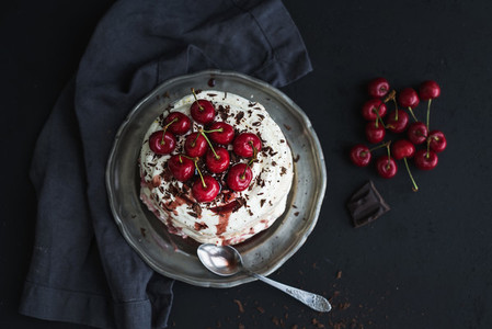 Pavlova cake with fresh cherry  cheese cream and chocolate chips in vintage silver plate over dark grunge background  top view