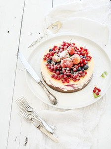 Cheesecake with fresh garden berries on top over white wooden table surface  Selective focus