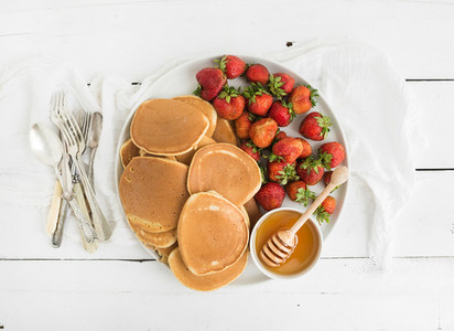 Breakfast plate  Homemade pancakes with fresh strawberry and honey  kitchen napkin  vintage silverware on rustic white background  Top view