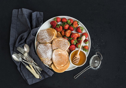 Breakfast plate  Homemade pancakes with fresh strawberry and honey  kitchen napkin  vintage silverware on dark grunge background  Top view