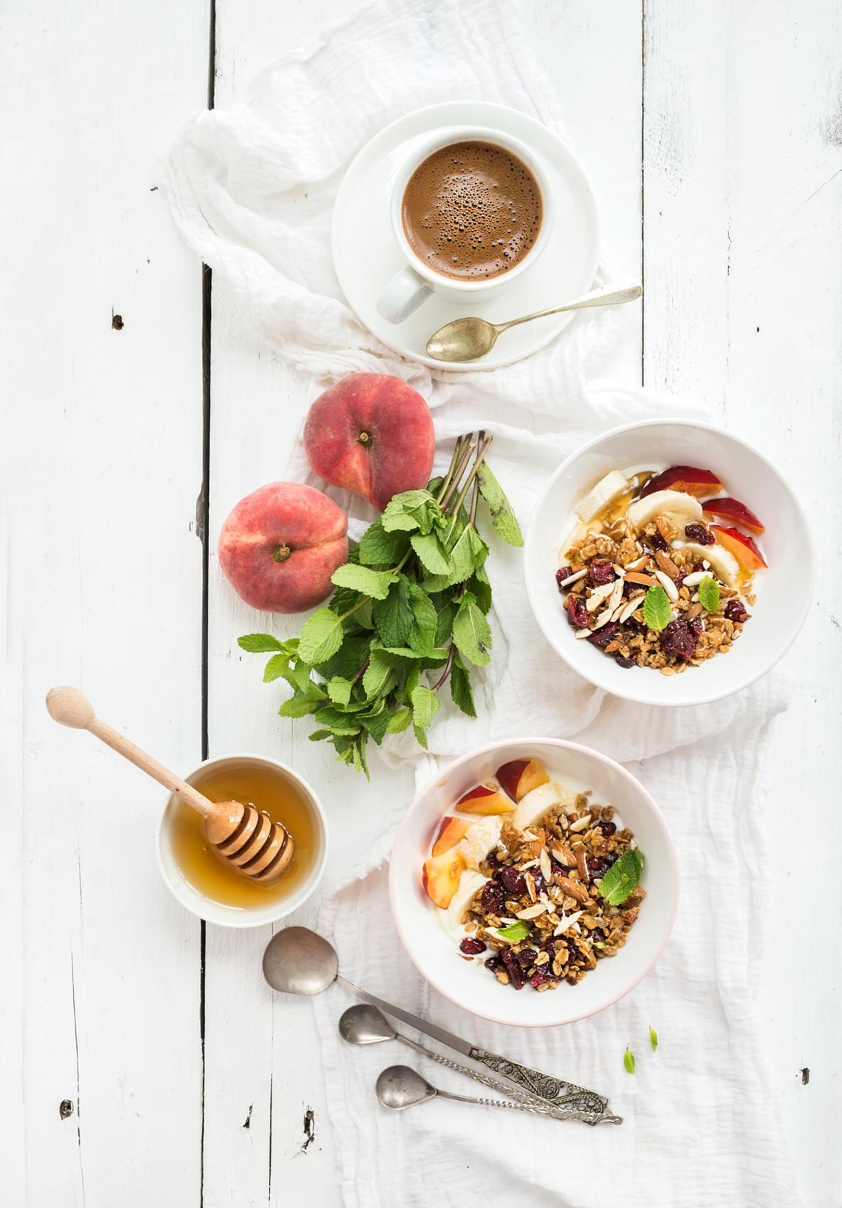 Healthy breakfast  Bowl of oat granola with yogurt  fresh fruit  mint and honey  Coffee  vintage silverware  Top view
