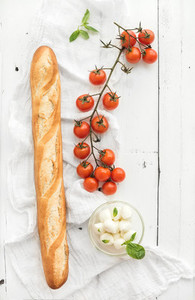 Baguette with banch of cherry tomatoes  basil and mozzarella cheese on rustic white wooden backdrop  top view