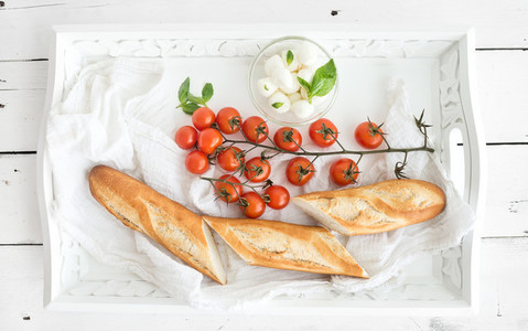 Baguette with branch of cherry tomatoes  basil and mozzarella cheese on rustic white wooden tray  top view