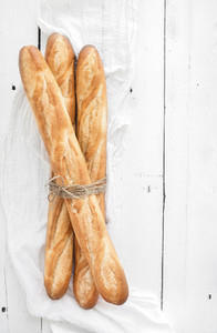 Freshly baked French baguettes on white wooden table  Top view