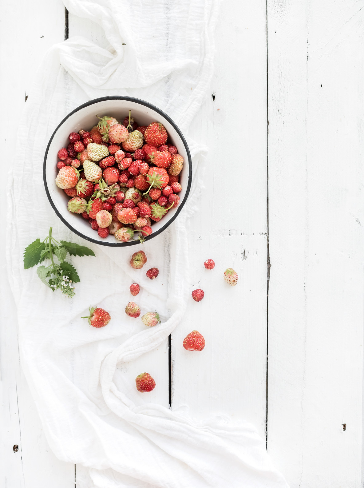 Wild strawberries in rustic metal bowl on white wooden background  top view