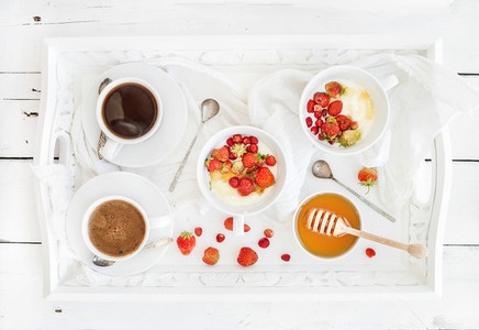 Healthy breakfast set  Yogurt  honey and wild srtawberry bowls with black coffee on serving tray over white rustic wooden backdrop