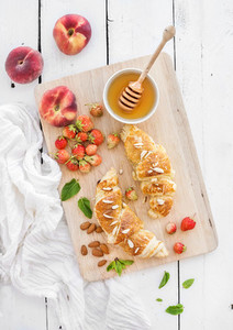Freshly baked almond croissants with garden strawberries peaches mint and honey on serving board over white rustic wood backdrop