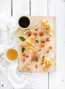 Freshly baked almond croissants with garden strawberries and honey on serving board over white rustic wood backdrop