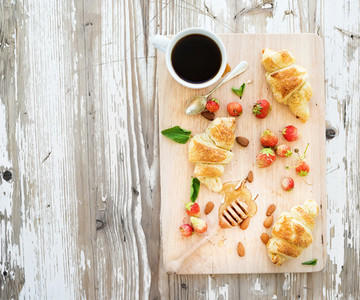 Freshly baked almond croissants with garden strawberries and honey on serving board over white rustic wood backdrop  top view