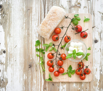 Ciabatta bread with banch of cherry tomatoes basil and mozzarella cheese on rustic wooden board over old white backdrop top view