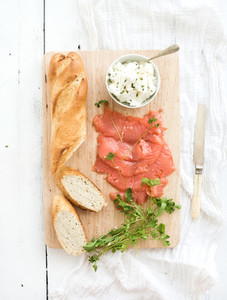 Salmon  ricotta and fresh parsley with baguette on a rustic wooden board over white wood background  Top view