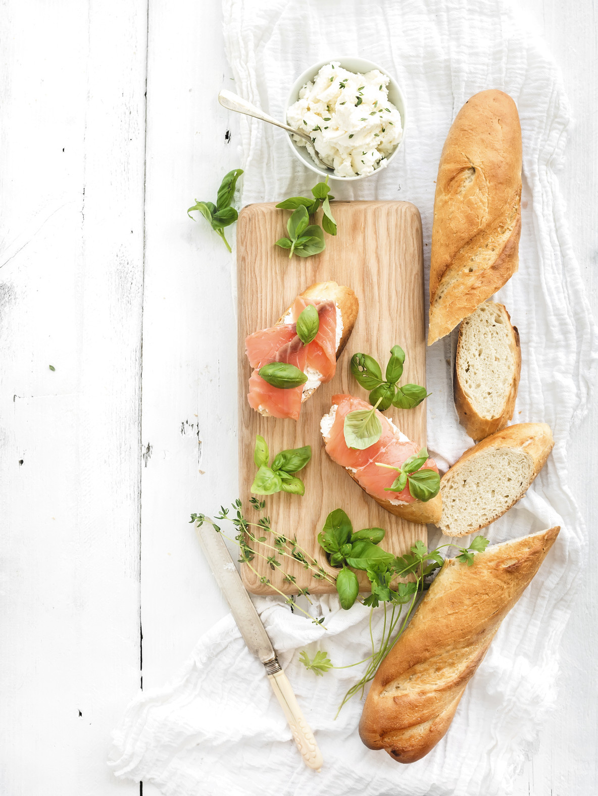 Salmon  ricotta and basil sandwiches with baguette on a rustic wooden board over white wood background  Top view