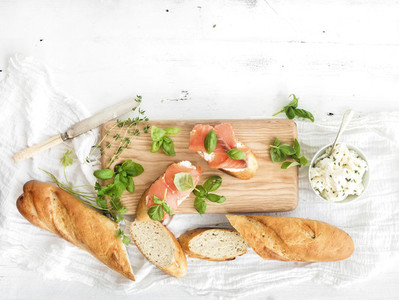 Salmon  ricotta and basil sandwiches with baguette on a rustic wooden board