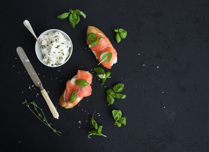 Salmon  ricotta and basil sandwiches over black grunge background  Top view