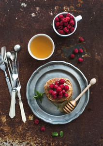 Breakfast set Buckwheat pancakes with fresh raspberries honey and mint leaves over grunge metal background top view