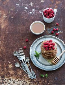 Breakfast set  Buckwheat pancakes with fresh raspberries  honey and mint leaves over grunge metal background