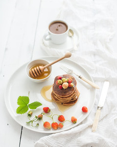 Breakfast set Buckwheat pancakes with fresh garden strawberries honey and cup of coffee over white wooden background