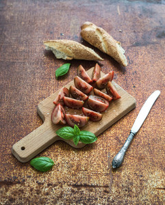 Ripe kumato tomatoes  basil leaves and knife on a rustic wooden chopping board over grunge rusty metal backdrop  top view
