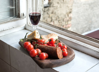 Home wine appetizer set  Glass of red wine  Hungarian spicy sausage  farmers cheese and cherry tomatoes in a ructic wooden dish placed near window