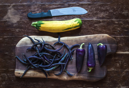 Violet chili peppers beans and yellow zucchini on rustic wooden chopping board over dark wood background