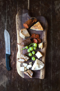 Wine appetizers set meat and cheese selection grapes bread on rustic wooden board over dark wood background Top view
