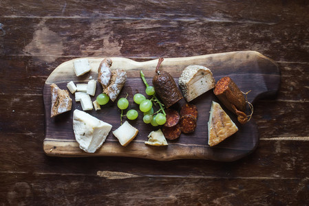 Wine appetizers set  meat and cheese selection  grapes  bread on rustic wooden board over dark wood background