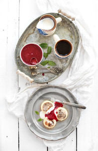 Breakfast set  Russian cottage cheese pancakes or syrniki on a vintage metal plate with raspberry jam  sour cream and coffee  Rustic white backdrop