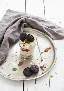 Yogurt oat granola with berries honey nuts and cookies in glass jar on vintage metal tray over rustic white  background
