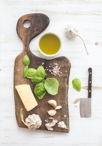 Pesto sauce cooking set  Fresh basil  olive oil  parmesan cheese and garlic on rustic walnut chopping board over white wooden backdrop