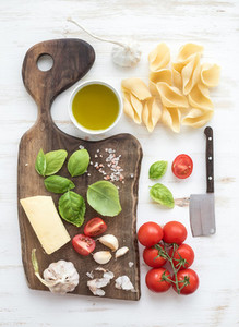 Ingredients for cooking pasta  Conchiglioni  basil leaves  cherry tomatoes  Parmesan cheese  olive oil  salt  garlic on rustic walnut chopping board over white wooden background