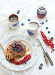 Breakfast set  Buckwheat pancakes with fresh berries  honey  sour cream and cup of coffee over white wooden background