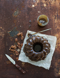 Chocolate coffee bundt cake with salt caramel icing over grunge rusty metal backdrop