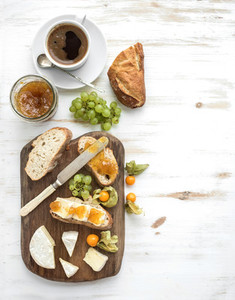 Breakfast set  Brie cheese and fig jam sandwiches with fresh grapes  ground cherries  Cup of coffee  Top view