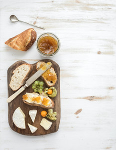 Breakfast set  Brie cheese and fig jam sandwiches with fresh grapes  ground cherries  Top view