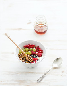 Healthy breakfast  Bowl of oat granola with yogurt  fresh berries  fruit and honey  Top view
